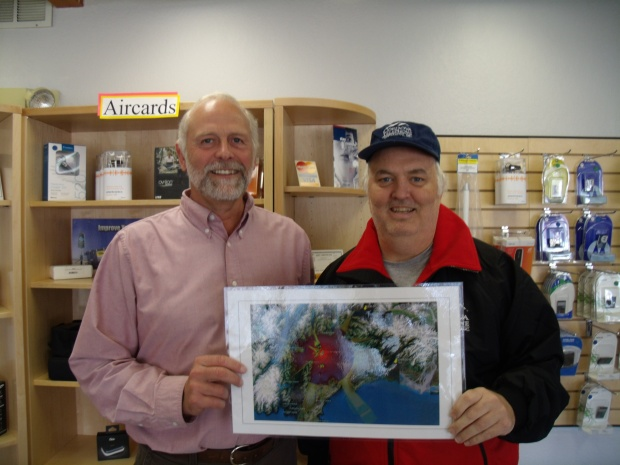 Paul Kelly & David Allison posing with a coverage map of the new CWC Naked Island cell tower in PWS